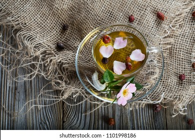 Rose hip herbal tea on a wooden surface. Free text. Closeup