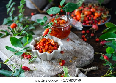 Rose hip jam in jar and ceramic pots on wooden board. Ripe red berries with leaves in plate and basket. Fresh vitamins on gray background. Exotic or rare food, Healthy nutrition, homemade marmalade