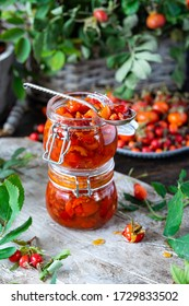 Rose hip jam in jar pots on wooden board. Ripe red berries with leaves in plate and basket. Fresh vitamins on gray background. Exotic or rare food, Healthy nutrition, homemade marmalade concept