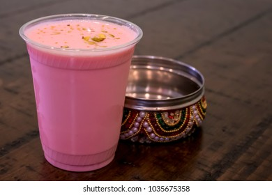 Rose Lassi with Pistachio Shavings in front of a Jeweled Spice Tin