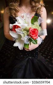 Rose and lily bouquet held by unrecognizable teenage girl wearing shimmering black prom gown