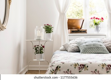 Rose loving woman's bedroom interior with a bed with flower pattern bedspread and pastel gray pillows. Red roses in pots on a stand by the bed. Real photo.