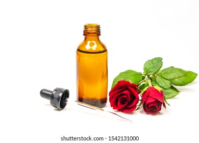 Rose oil in bottle and rose flower isolated on white background. Essential oil product concept.
