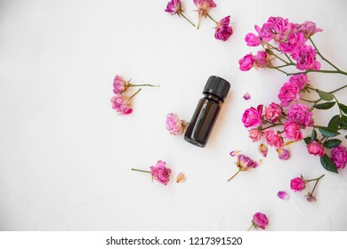 Rose oil bottle with roses, top view, spa treatment and skincare oil