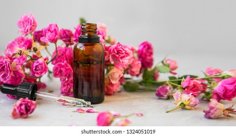 Rose oil. Spa and aromatherapy rose flowers essential oil bottle with pipette