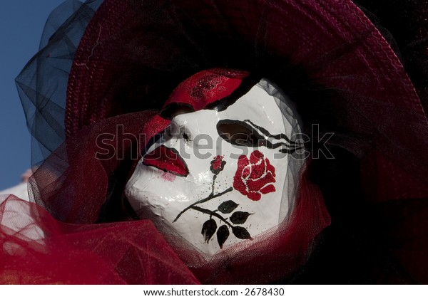 A rose painted on a red and white venetian mask
