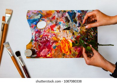 Rose and palette in hands, against the background of brushes and colored pallets. View from above. Artist's work.
