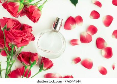Rose perfume bottle with fresh pink flower petals, top viewed white background. Soft delicate tones.