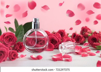 Rose perfume bottle surrounded by pink fresh rosebuds and falling petals. Floral feminine scent, beautiful dreamlike background