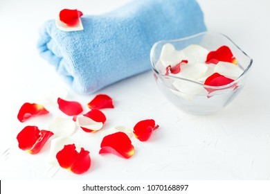 Rose petals in a glass bowl with water and a towel. SPA concept, cosmetics, procedure, treatment.