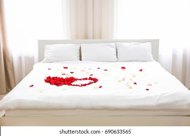 Rose petals on bed in hotel room
