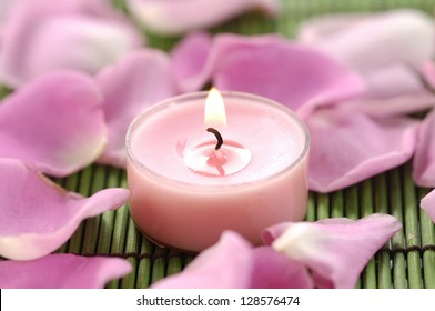rose petals and pink candle on green mat