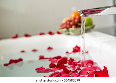 Rose petals put in bathtub for romantic bathroom in honeymoon suit.Arranged by interior designer for honeymoon couple. Scent of rose make relax. Spa shop put flowers in the tub with towels for lover.