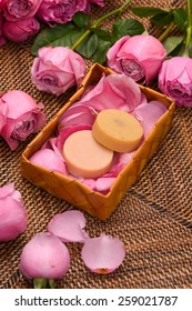 rose and petals with soap in basket on mat
