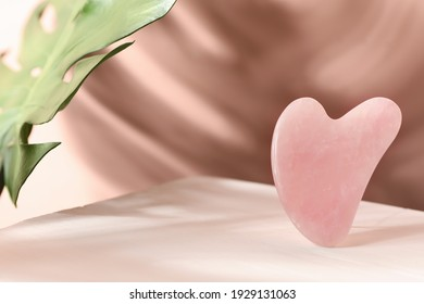 Rose quartz gua sha tool and tropical leaf on table, space for text