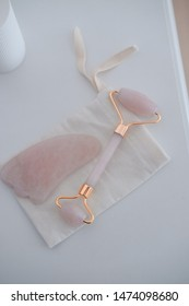 Rose quartz guasha stone and roller. Beauty anti-ageing concept. Top view