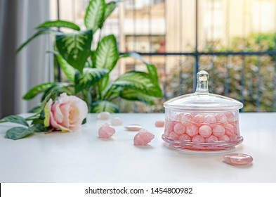 Rose quartz small balls charge spring water with their energy in a glass jar. The water absorbs energy vibrations from the crystals. There are stone rabbits, hearts and flowers on the balcony table.
