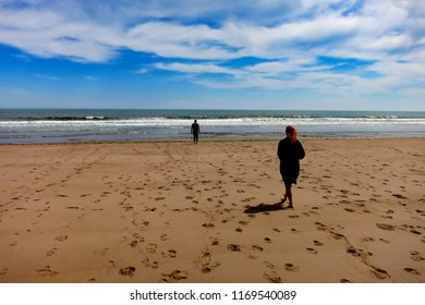 rose sandy beach St Cyrus Nature Reserve Lunan bay Montrose Scotland with a couple walking  in the ocean
