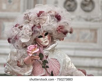 Rose Venice carnival mask holding the pink rose on light blurred background.
