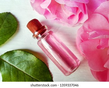 Rose water for skincare in bottle, fresh rose flowers - floral hydrosol pure natural extract. Rose water cleanser recipe, skin & face care, hair, massage, aromatherapy, spa. Closeup rose attar water