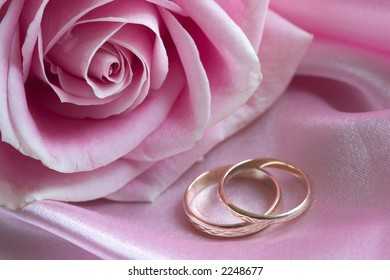 rose and wedding bands on pink