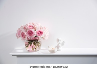 Rose White Pink O'hara in the glass transparent vase with figurine of bird and the smal candle. The pink box with valentine gift is on the fireplace. Copy space