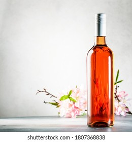 Rose wine bottle on the gray table and spring pink flowers. Rosado, rosato or blush wine tasting in wineshop, bar concept. Copy Space
