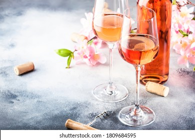 Rose wine glass with bottle on the gray table and pink flowers. Rosado, rosato or blush wine tasting in wineshop, bar concept. Copy Space