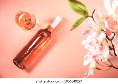 Rose wine glass with bottle on blush background and pink flowers. Rosado, rosato pink wine tasting