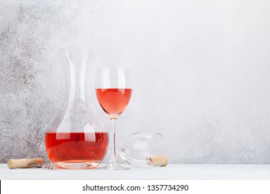 Rose wine in glass and decanter on wooden table. In front of stone wall with space for your text
