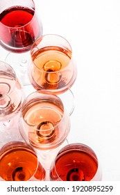 Rose wine glasses set on wine tasting. Degustation different varieties, colors and shades of pink wine concept. White background, top view