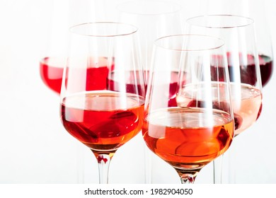 Rose wine glasses set on wine tasting. Different varieties, colors and shades of pink wines on white background
