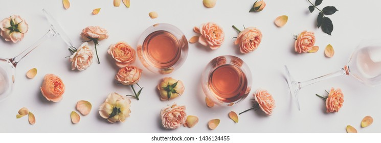 Rose wine and roses on white background, flat lay