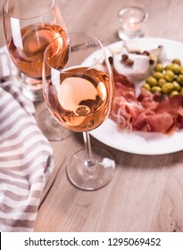 Rose wine and snacks. Two glasses wine on wooden table. Plate green olives, jamon and cheese on a plate. French alcohol drinks with homemade cheese.