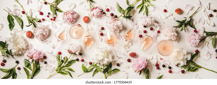 Rose wine variety layout. Flat-lay of rose wine in various glasses with flowers and summer fruit over plain white background, top view. Summer drink for party, wine shop or wine tasting concept - Shutterstock ID 1779504419