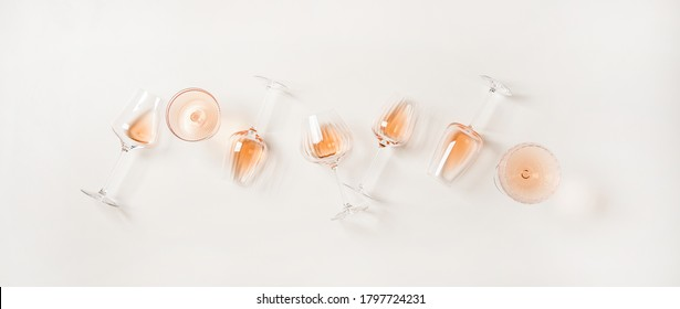 Rose wine variety layout. Flat-lay of rose wine in various glasses over plain white background, top view. Summer drink for party, wine shop or wine tasting concept