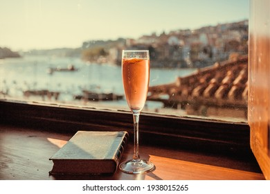 Rose wine and vintage book on window sill with cityscape of Porto, Portugal. Boats on river Douro and historical buildings in view of tourist.