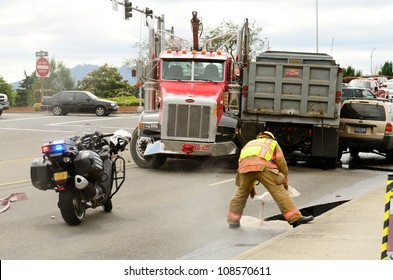 ROSEBURG, OR - JULY 20: Fire fighters spreading absorbent at a four vehicle accident involving two large trucks resulted in a single injury and a diesel fuel spill. July 20, 2012 in Roseburg Oregon