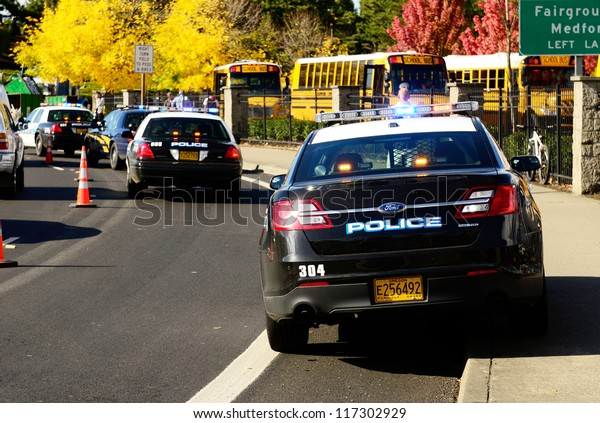 ROSEBURG, OR - OCTOBER 16: Police cars and school buses at an accident at the entrance of the High School loading zone in Roseburg Oregon, October 16, 2012