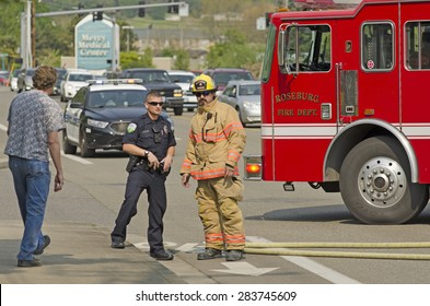 Roseburg, OR, USA - April 2, 2015: Firefighters respond to a two vehicle accident with on car on fire.