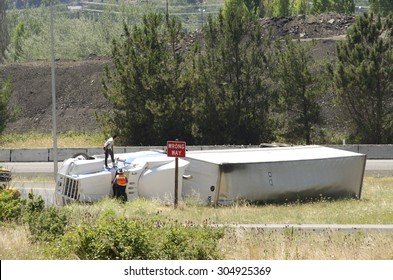 Roseburg, OR, USA - July 7, 2014: Large semi truck overturns on a freeway exit ramp