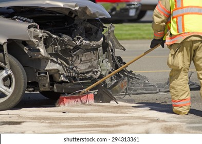ROSEBURG, OR, USA - June, 10, 2015: A fire fighter cleans up fluids at the scene of a two vehicle accident with heavy head on damage