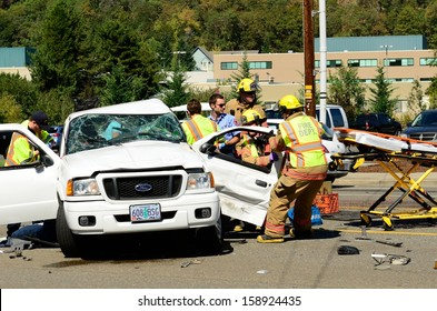 ROSEBURG, OR - SEPTEMBER 11, 2013: Firefighters extricate victims of a two vehicle t-bone accident at an intersection resulted in major injuries in Roseburg, Oregon on September 11, 2013