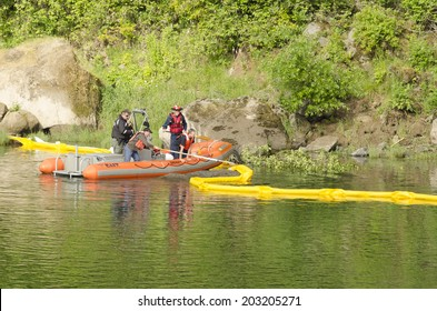 ROSEBURG, USA, USA - JUNE 02, 2014: Roseburg Hazardous materals team use a Douglas County Sheriff boat to deploy a floating oil containment boom on the Umpqua River following an vehicle accident