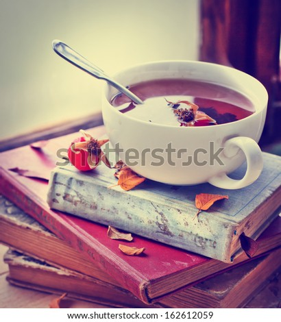 rosehip tea on old books/tea home with books/romantic autumn vintage background with books and tea/cup of tea with hip roses on wooden table