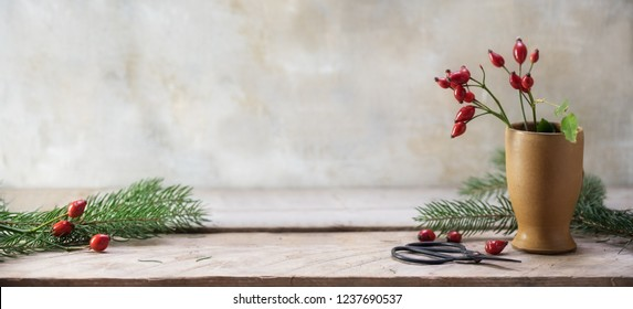 rosehips and fir branches in a stoneware vase and on a rustic wooden table to arrange christmas decoration, vintage background with copy space, panoramic banner format, selected focus