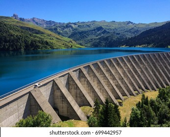 The Roseland Dam holds back a deep blue reservoir of water as a white car drives across the top towards the French Alps.