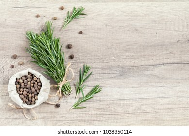 Rosemary bunch of bouquets and spices fragrant pepper on light wooden surface. Top view, copy space.