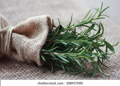 Rosemary bunch nestled inside a burlap bag tied with twine.