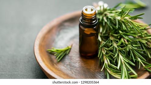 Rosmarin ätherische Ölflasche mit rosmarinem Kräuterbrot auf Holzteller, Aromatherapie Kräuteröl